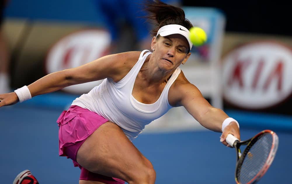 Casey Dellacqua of Australia makes a forehand return to Eugenie Bouchard of Canada during their fourth round match at the Australian Open tennis championship in Melbourne.