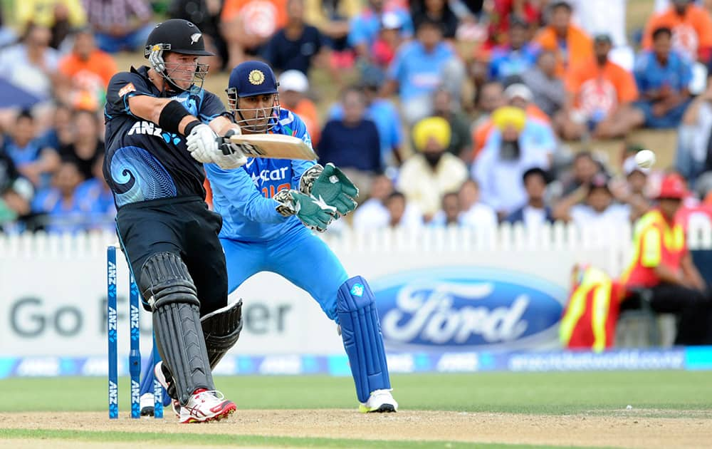 New Zealand's Corey Anderson, left, hits a boundary in his innings of 44 off 17 balls in front of India's MS Dhoni in the second one-day International cricket match at Seddon Park in Hamilton, New Zealand.