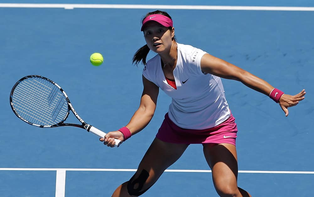 Li Na of China looks at a ball for a volley to Eugenie Bouchard of Canada during their semifinal at the Australian Open tennis championship in Melbourne, Australia.