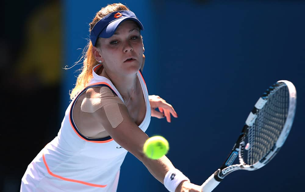 Agnieszka Radwanska of Poland makes a backhand return to Dominika Cibulkova of Slovakia during their semifinal at the Australian Open tennis championship in Melbourne.