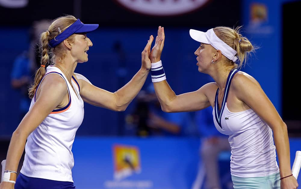 Russia's Ekaterina Makarova, left, and Elena Vesnina celebrate a point won over Italy's Sara Errani and Roberta Vinci during their women's doubles final at the Australian Open tennis championship in Melbourne.