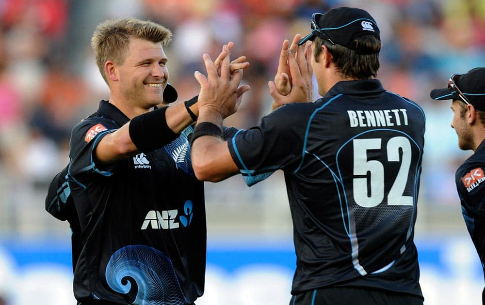 New Zealand's Corey Anderson, left, celebrates with Hamish Bennett after he took the catch off his bowling to dismiss India's Rohit Sharma for 39 in the third one-day International cricket match at Eden Park in Auckland.