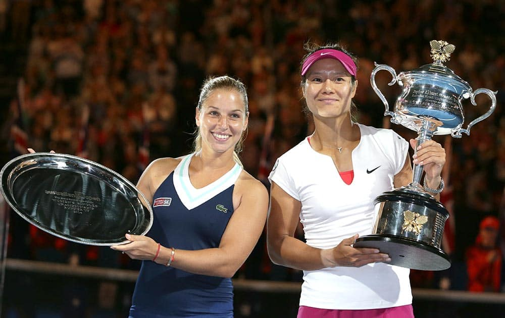 Li Na of China, holds the championship trophy with second placed Dominika Cibulkova of Slovakia in their women's singles final at the Australian Open tennis championship in Melbourne.