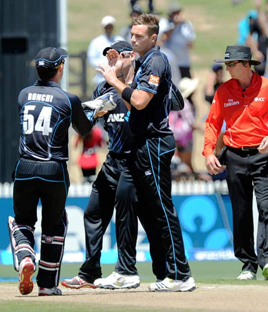 New Zealand's Tim Southee, right, celebrates after dismissing India's Virat Kohli for 2 in the fourth one-day international cricket match at Seddon Park in Auckland.