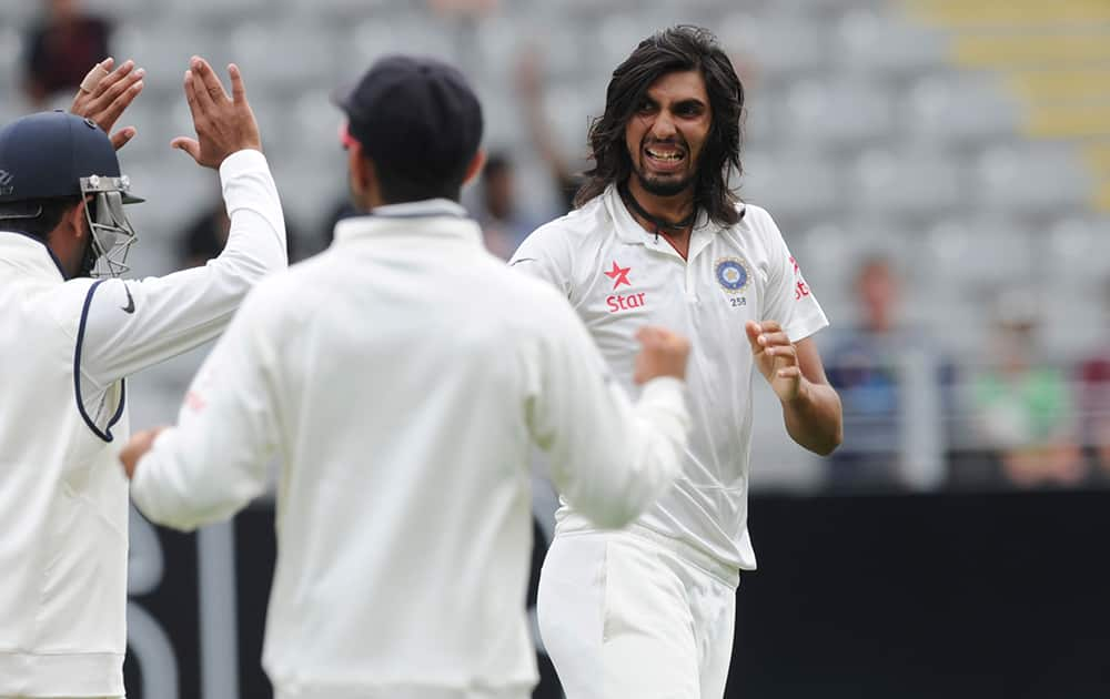 India's Ishant Sharma, right, celebrates with team mates after dismissing New Zealand's Ross Taylor for 3 in the first cricket test at Eden Park in Auckland, New Zealand.