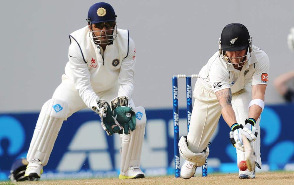 New Zealand's Brendon McCullum bats in front of India's wicket keeper MS Dhoni on the first day of the first cricket test at Eden Park in Auckland, New Zealand.