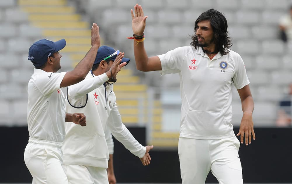 India's Ishant Sharma gives high five with team mates after dismissing New Zealand's BJ Watling for 1 on the second day of the first cricket test at Eden Park in Auckland, New Zealand.
