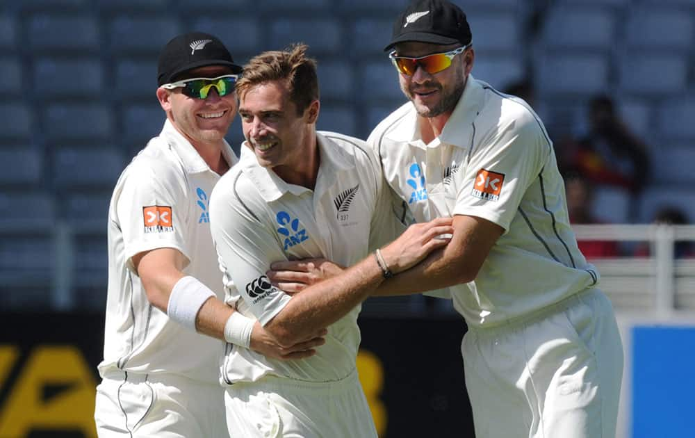 New Zealand's Tim Southee, center, with Corey Anderson, left and Peter Fulton after dismissing India's Rohit Sharma for 19 on the fourth day of the first cricket test, at Eden Park in Auckland, New Zealand.