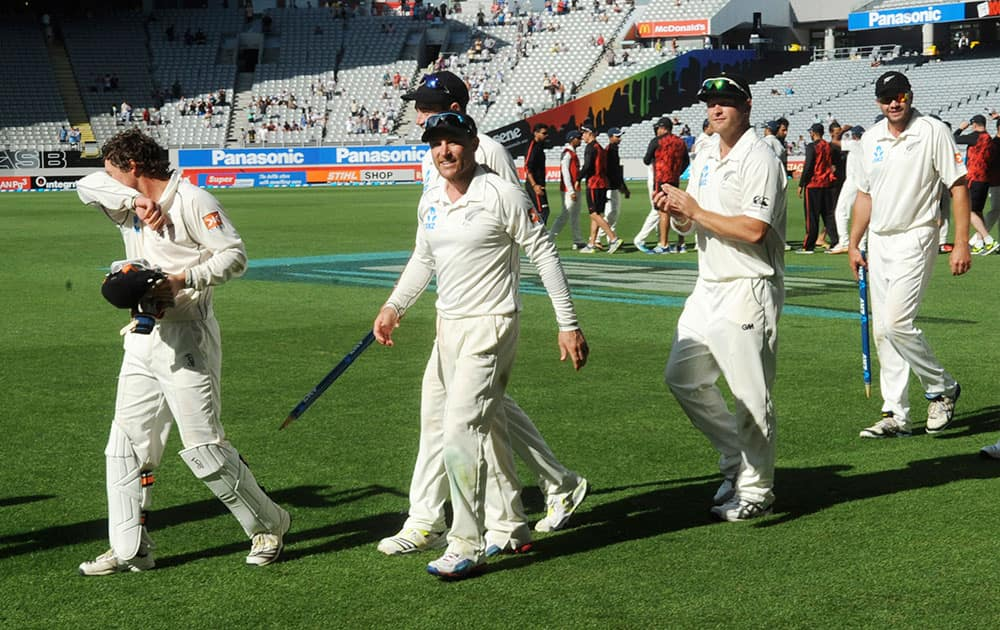 New Zealand's Brendon McCullum, center, walks with his team after their 40 run defeat of India on the fourth day of the first cricket test at Eden Park in Auckland, New Zealand.