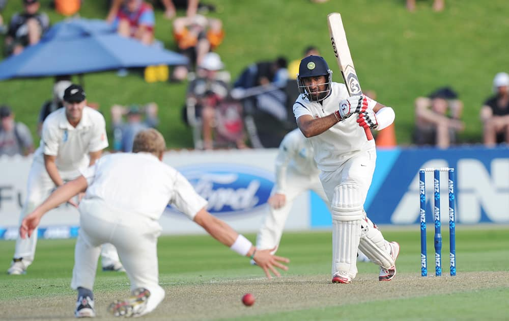 India's Cheteshwar Pujara bats the ball pats New Zealand's Neil Wagner on the first day of the second cricket test in Wellington, New Zealand.