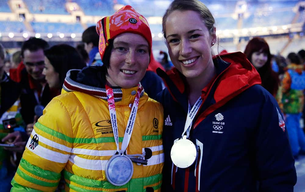 Britain's Elisabeth Yarnold, right, and Germany's Marion Thees pose for a photograph during the closing ceremony of the 2014 Winter Olympics.