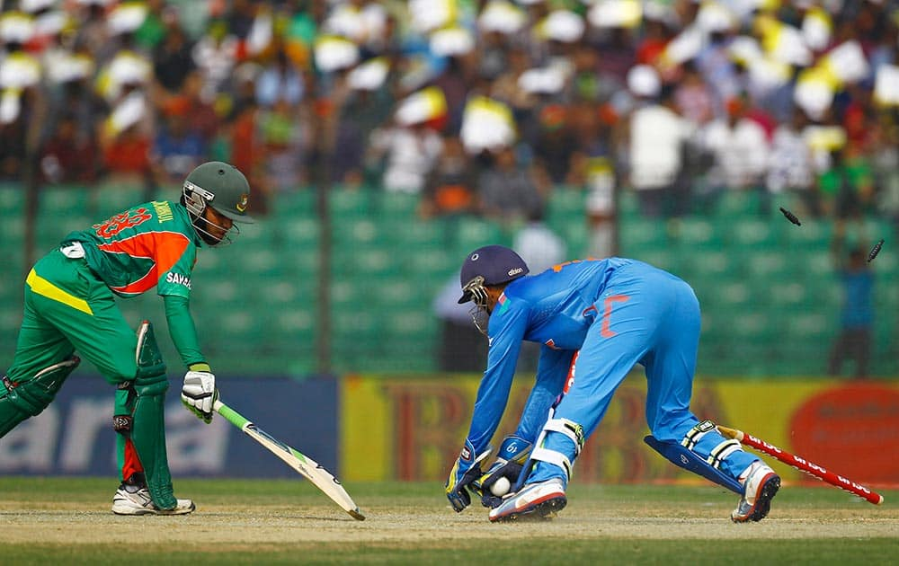 India's Dinesh Karthik, right, successfully dislodges the bails to dismiss Bangladeshi Mominul Haque during the Asia Cup one-day international cricket tournament in Fatullah, near Dhaka, Bangladesh.