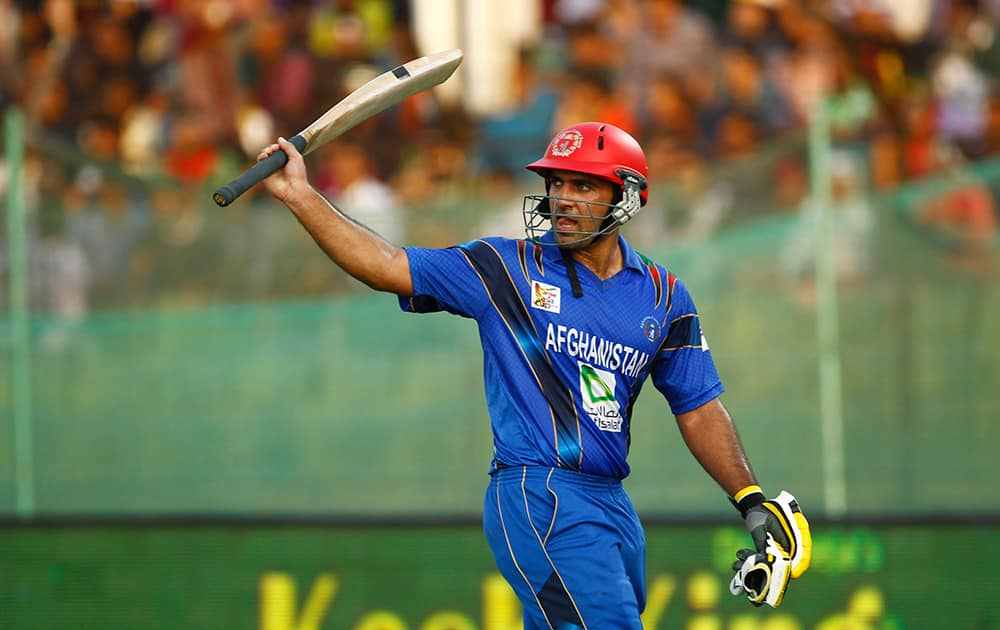 Afghanistan's Samiullah Shenwari acknowledges the crowd as he walks back to the pavilion after his dismissal during the Asia Cup one-day international cricket tournament against Bangladesh in Fatullah, near Dhaka, Bangladesh.