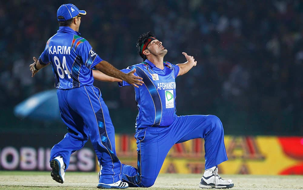 Afghanistan's Hamid Hassan, right, and his teammate Karim Sadiq celebrate the wicket of Bangladesh's Anamul Haque during the Asia Cup one-day international cricket tournament in Fatullah, near Dhaka, Bangladesh.