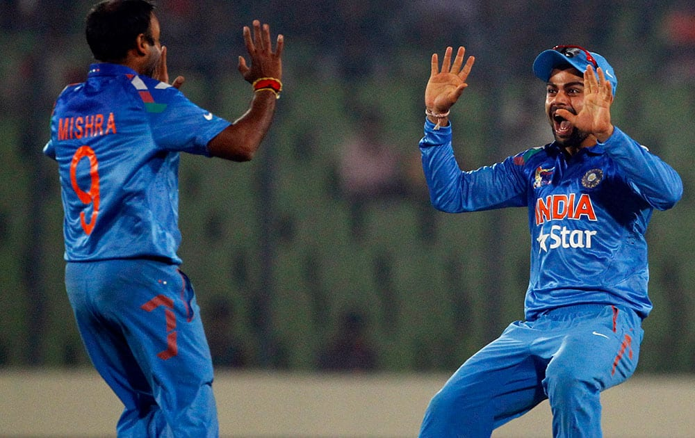 Amit Mishra, left, celebrates with teammate Virat Kohli after taking the wicket of Pakistan's Ahmed Shehzad during the Asia Cup one-day international cricket tournament in Dhaka.