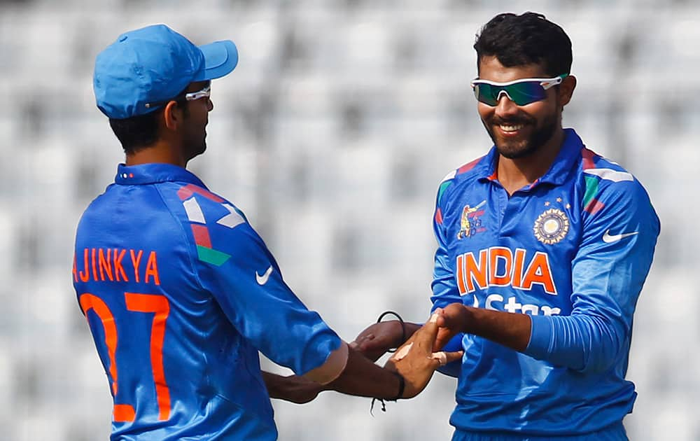 Ravindra Jadeja celebrates with his teammate Ajinkya Rahane after the dismissal of Afghan cricket player Asghar Stanikzai during the Asia Cup one-day international cricket tournament against India in Dhaka, Bangladesh.
