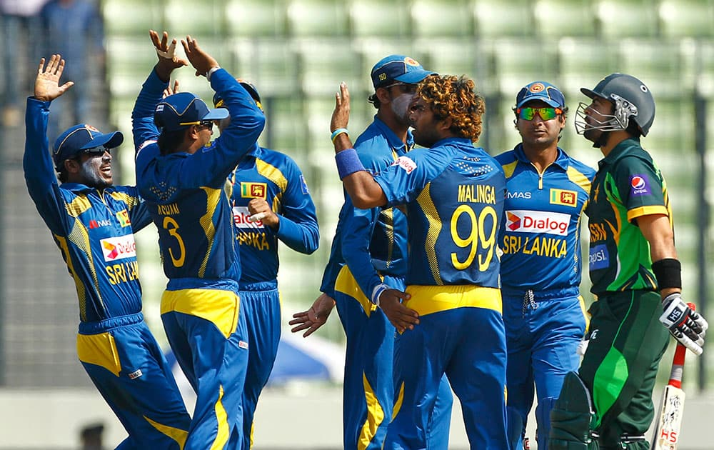 Sri Lankan cricket player Lasith Malinga, third right, celebrate with his teammates after taking the wicket of Pakistan's Ahmed Shehzad, right, during the Asia Cup final cricket match against Pakistan in Dhaka.