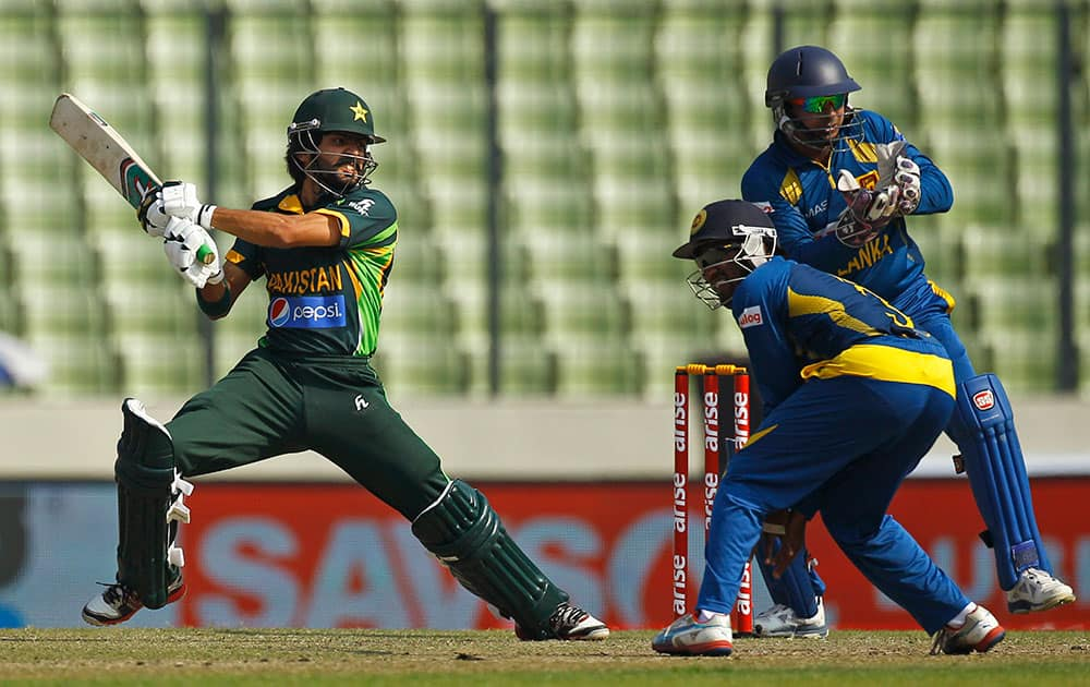 Pakistan's Fawad Alam, left, plays a shot in front of Sri Lankan wicketkeeper Kumar Sangakkara, right, and a teammate during their Asia Cup final cricket match in Dhaka, Bangladesh.