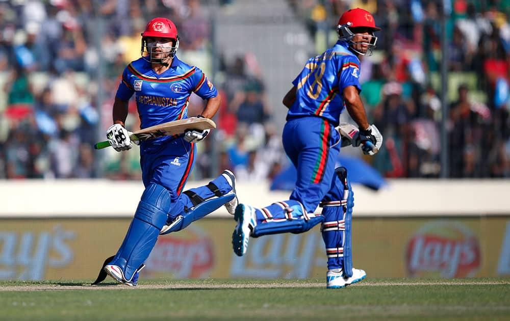 Afghanistan's batsmen Gulbadin Naib, left, and Najibullah Taraki run between the wickets during the ICC Twenty20 Cricket World Cup opening match against Bangladesh in Dhaka.