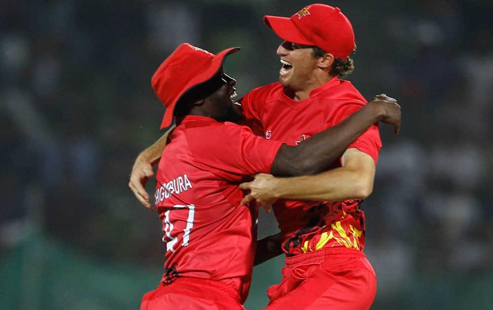 Zimbabwe's Elton Chigumbura, left, celebrates with a teammate the wicket of Ireland's Max Sorensen during their ICC Twenty20 Cricket World Cup match in Sylhet, Bangladesh.