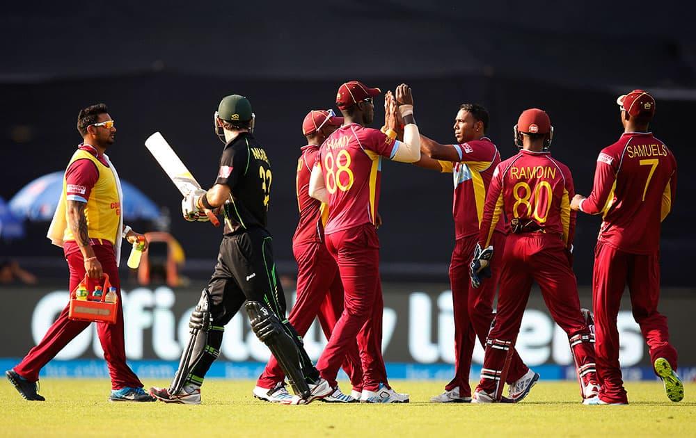 West Indies' bowler Samuel Badree, third right, celebrates with teammates the dismissal of Australia's batsman Glenn Maxwell, second left, during their ICC Twenty20 Cricket World Cup match in Dhaka, Bangladesh.