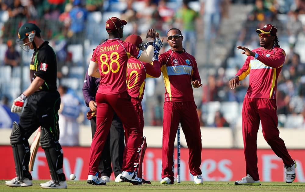 West Indies' bowler Marlon Samuels celebrates with teammates the dismissal of Australia's captain George Bailey during their ICC Twenty20 Cricket World Cup match in Dhaka, Bangladesh.