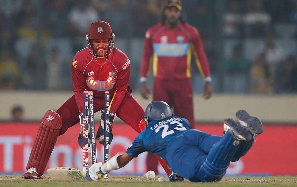 Sri Lanka's batsman Tillakaratne Dilshan, on ground, is run out by West Indies' Lendl Simmons, unseen, as wicketkeeper Denesh Ramdin looks on during their ICC Twenty20 Cricket World Cup semi-final match in Dhaka.