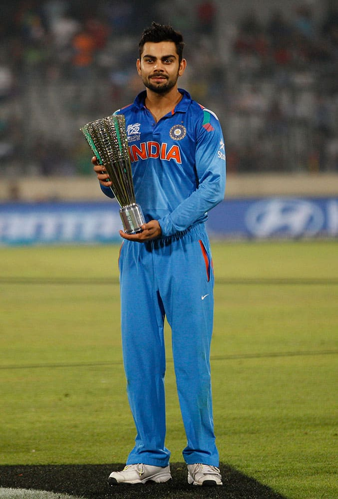 India's Virat Kohli poses with the Player of the Tournament trophy after his team's loss in the ICC Twenty20 Cricket World Cup final match against Sri Lanka in Dhaka.