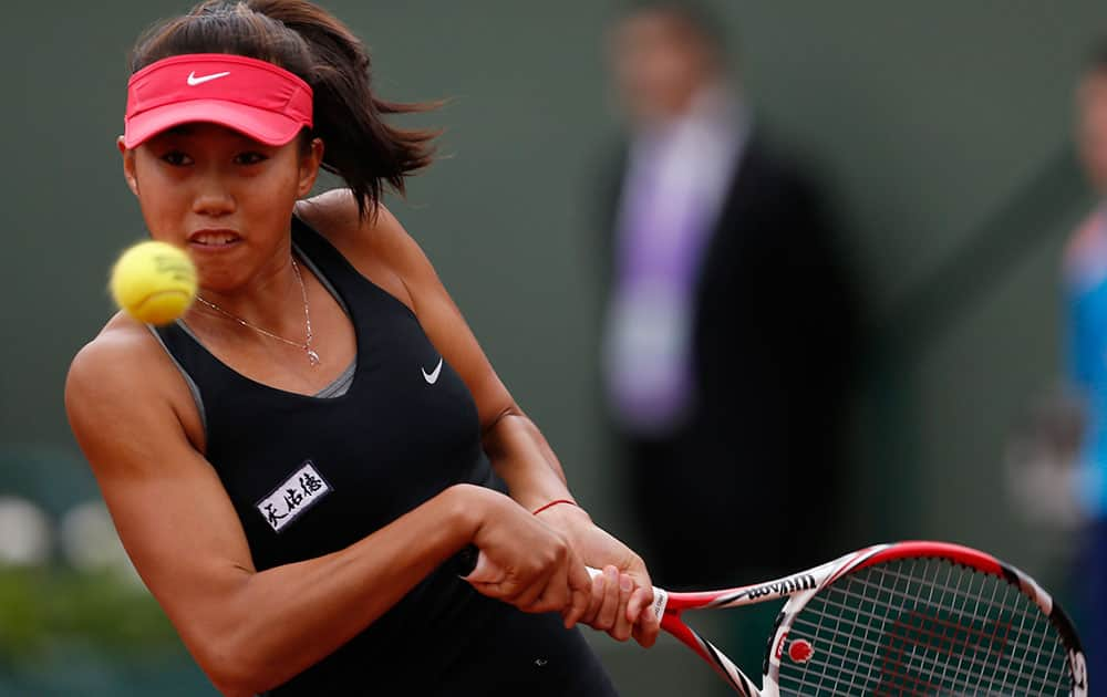 China's Zhang Shuai returns the ball to Poland's Agnieszka Radwanska during the first round match of the French Open tennis tournament at the Roland Garros stadium, in Paris.