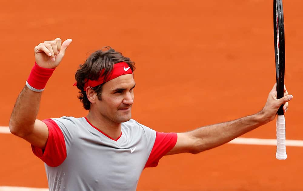 Switzerland's Roger Federer thumbs up after defeating Slovakia's Lukas Lacko in the first round match of the French Open tennis tournament at the Roland Garros stadium, in Paris.