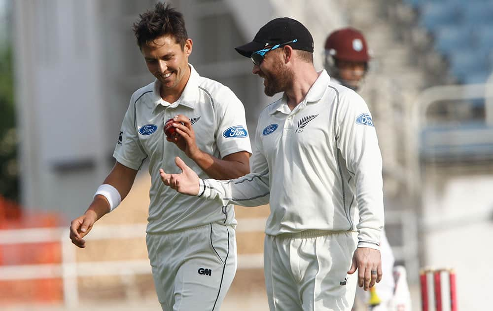 New Zealand's bowler Trent Boult, left, talk with captain Brendon McCullum during the second day of their first cricket Test match against West Indies in Kingston, Jamaica.