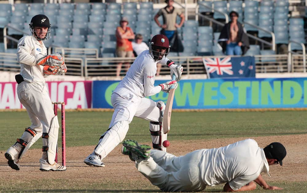 New Zealand's Ross Taylor, on ground, dives in an attempt to catch West Indies batsman Shane Shillingford, center, as New Zealand's wicket keeper BJ Watling, left, look on during the second innings on the fourth day of their first cricket Test match in Kingston, Jamaica.