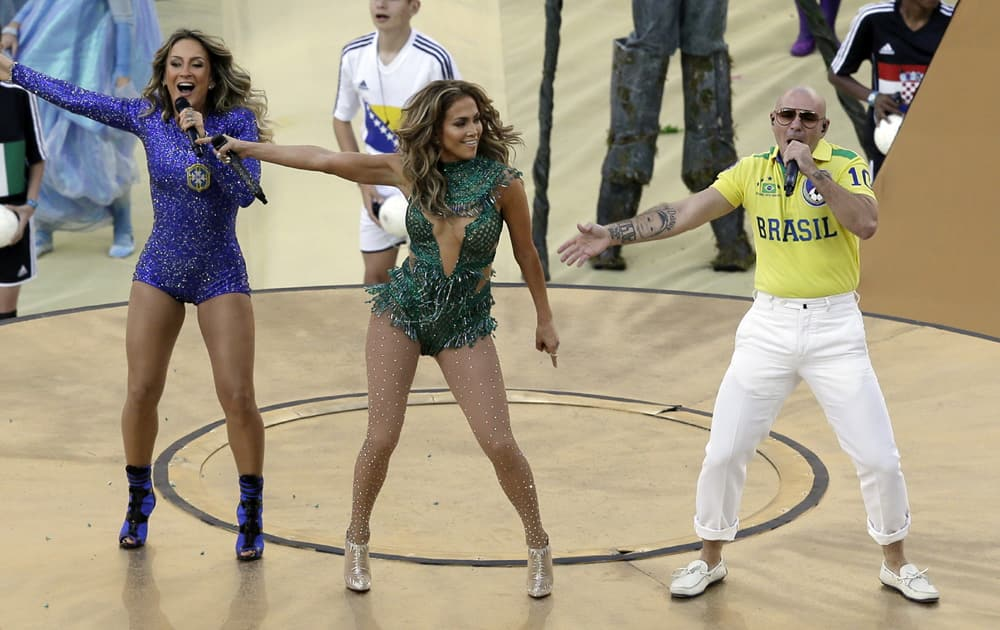 Brazilian singer Claudia Leitte, left, US singer Jennifer Lopez and rapper Pitbull perform during the opening ceremony ahead of the group A World Cup soccer match between Brazil and Croatia, the opening game of the tournament, in the Itaquerao Stadium in Sao Paulo, Brazil.