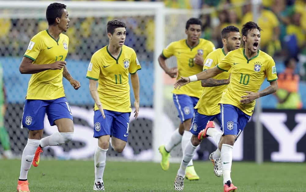 Brazil's Neymar celebrates with teammates after scoring during the group A World Cup soccer match between Brazil and Croatia, the opening game of the tournament, in the Itaquerao Stadium in Sao Paulo, Brazil.