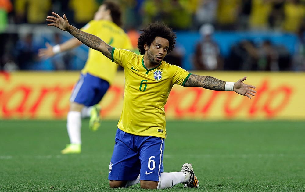 Brazil's Marcelo celebrates after Oscar scored the 3rd goal during the group A World Cup soccer match between Brazil and Croatia, the opening game of the tournament, in the Itaquerao Stadium in Sao Paulo, Brazil