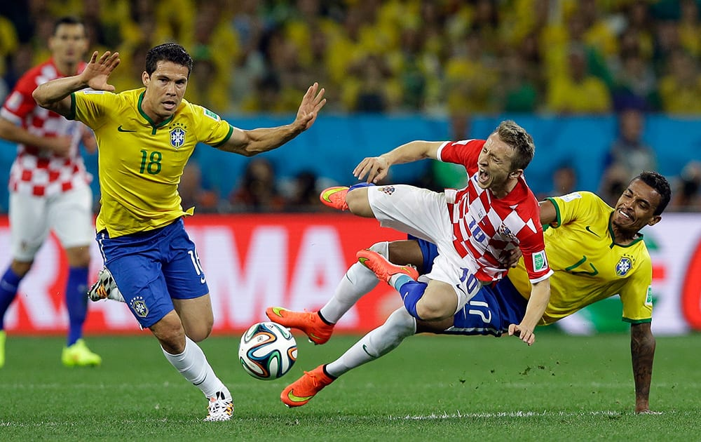 Croatia's Luka Modric, centre, is fouled by Brazil's Luiz Gustavo, right, during the group A World Cup soccer match between Brazil and Croatia, the opening game of the tournament, in the Itaquerao Stadium in Sao Paulo, Brazil.