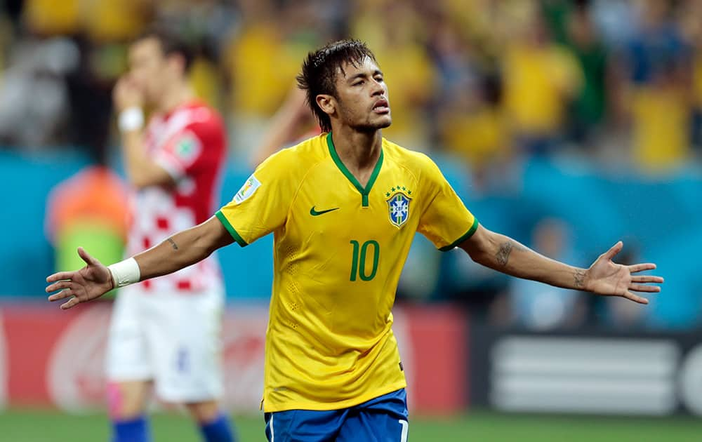 Brazil's Neymar celebrates his second goal on a penalty kick during the group A World Cup soccer match between Brazil and Croatia, the opening game of the tournament, in the Itaquerao Stadium in Sao Paulo, Brazil