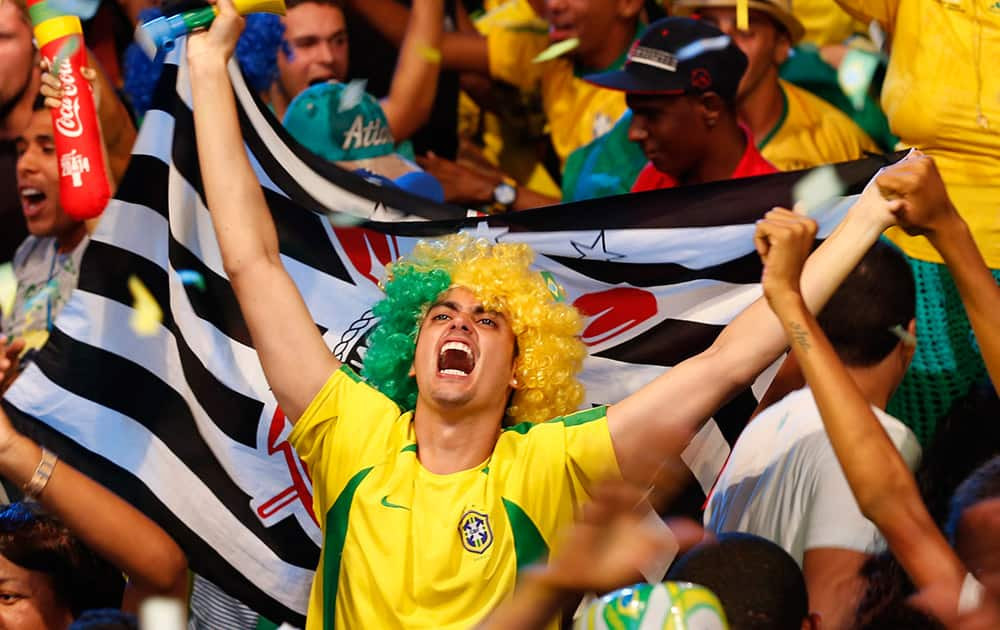 A Brazilian fan celebrates as he watches the 2014 soccer World Cup opening game between Brazil and Croatia at the Fan Fest complex in Recife, Brazil.