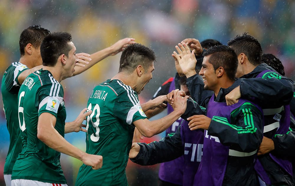 Mexico's Oribe Peralta, center, is congratulated by teammates after his goal during the second half of the group A World Cup soccer match between Mexico and Cameroon in the Arena das Dunas in Natal, Brazil