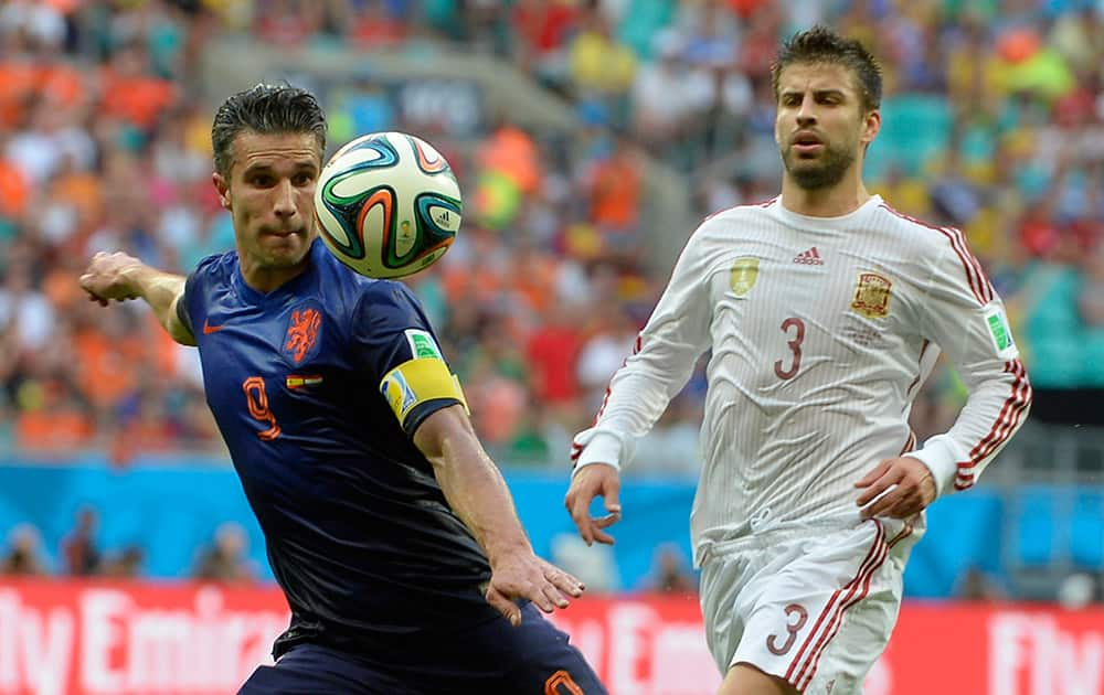 Netherlands' Robin van Persie, left, prepares to take a shot watched by Spain's Gerard Pique during the group B World Cup soccer match between Spain and the Netherlands at the Arena Ponte Nova in Salvador, Brazil.