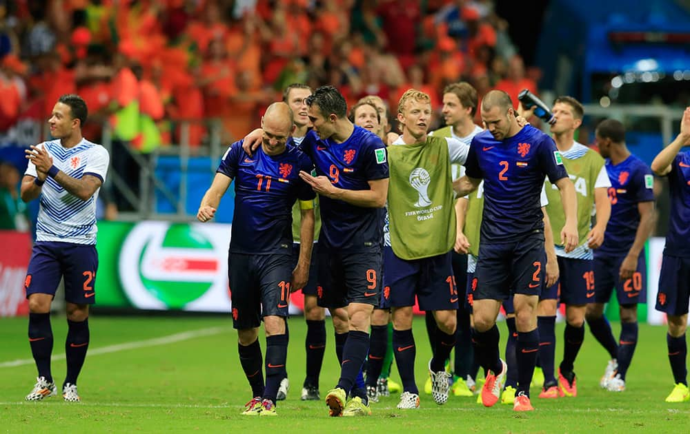 Dutch players celebrate after the group B World Cup soccer match between Spain and the Netherlands at the Arena Ponte Nova in Salvador, Brazil.. The Netherlands won the match 5-1.
