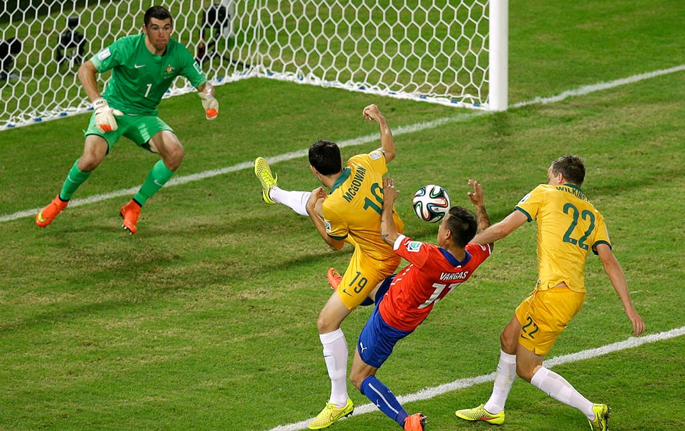 Chile's Eduardo Vargas, second right, fights for the ball with Australia's Ryan McGowan, left, and Australia's Alex Wilkinson during the group B World Cup soccer match between Chile and Australia in the Arena Pantanal in Cuiaba, Brazil.