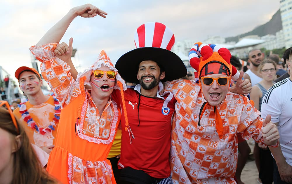 Dutch soccer fans pose for a photo with a Chilean soccer fan, center, while watching the live broadcast of the World Cup match between Spain and the Netherlands, inside the FIFA Fan Fest area on Copacabana beach in Rio de Janeiro, Brazil.