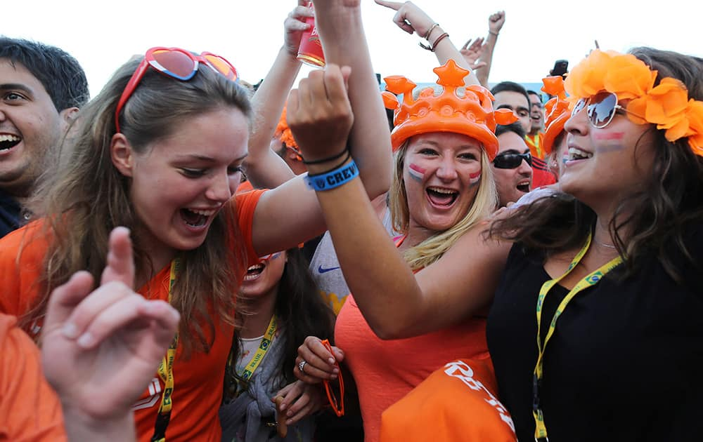Netherlands soccer fans celebrates their team's goal against Spain as they watch the World Cup match inside the FIFA Fan fest area on Copacabana beach in Rio de Janeiro, Brazil.