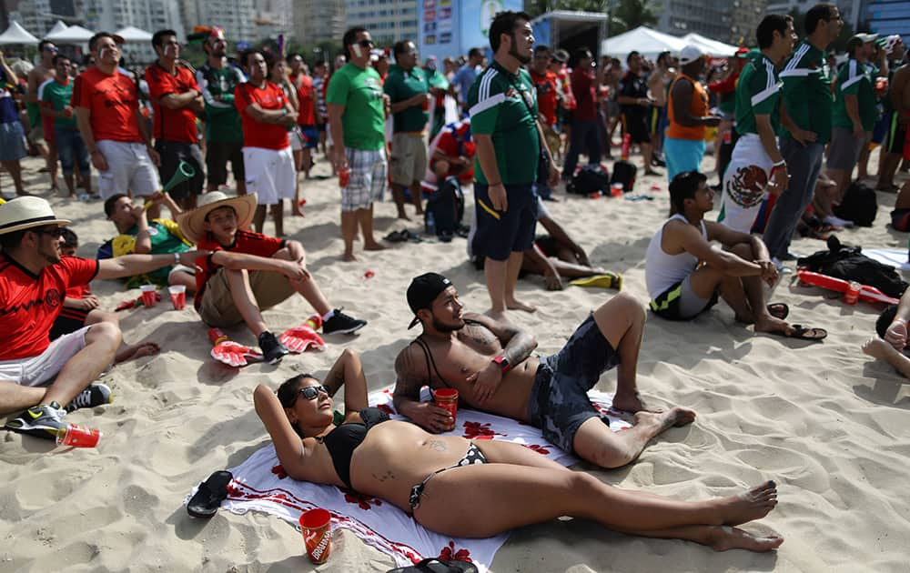 A Mexico soccer fan sunbathes as she watches her team's World Cup match with Cameroon inside the FIFA Fan fest area on Copacabana beach, in Rio de Janeiro, Brazil.