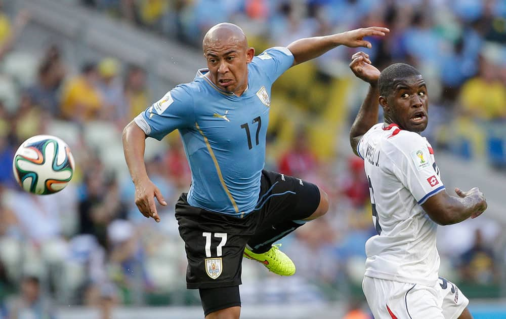 Uruguay's Egidio Arevalo Rios, left, and Costa Rica's Joel Campbell battle for the ball during the group D World Cup soccer match between Uruguay and Costa Rica at the Arena Castelao in Fortaleza, Brazil.