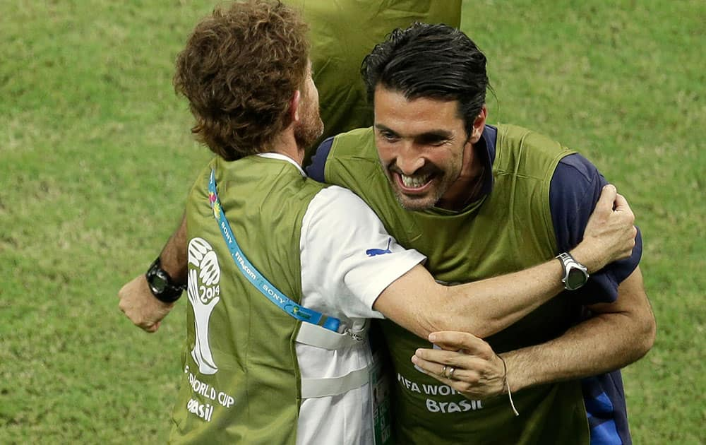 Italy's injured goalkeeper Gianluigi Buffon celebrates with teammates after Italy's Mario Balotelli scored his side's 2nd goal during the group D World Cup soccer match between England and Italy at the Arena da Amazonia in Manaus, Brazil.