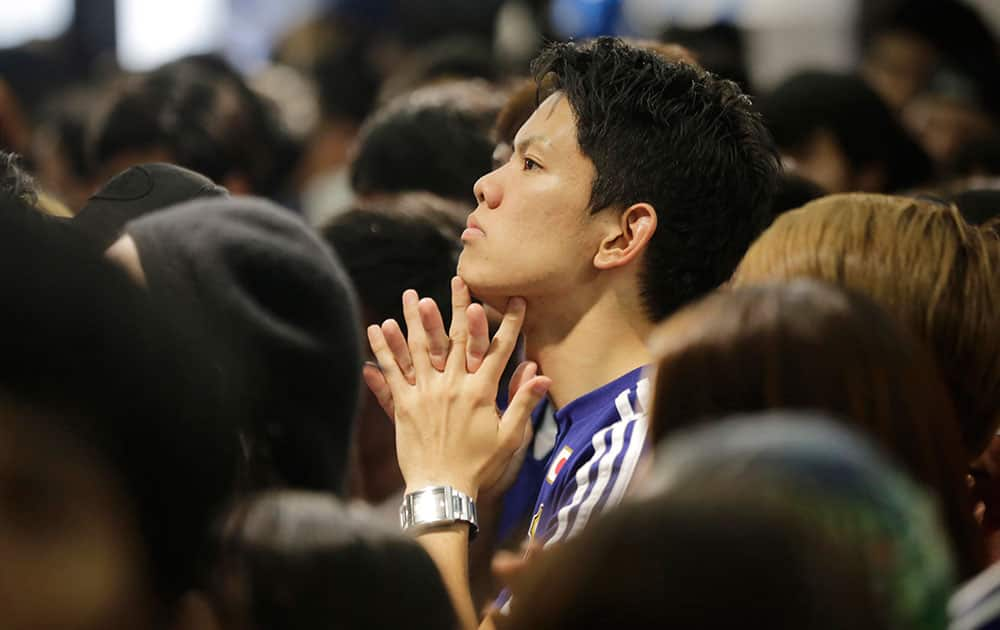 Japanese soccer fans are dejected during a live broadcast of the group C World Cup soccer match between Japan and Ivory Coast at a public viewing venue in Tokyo.