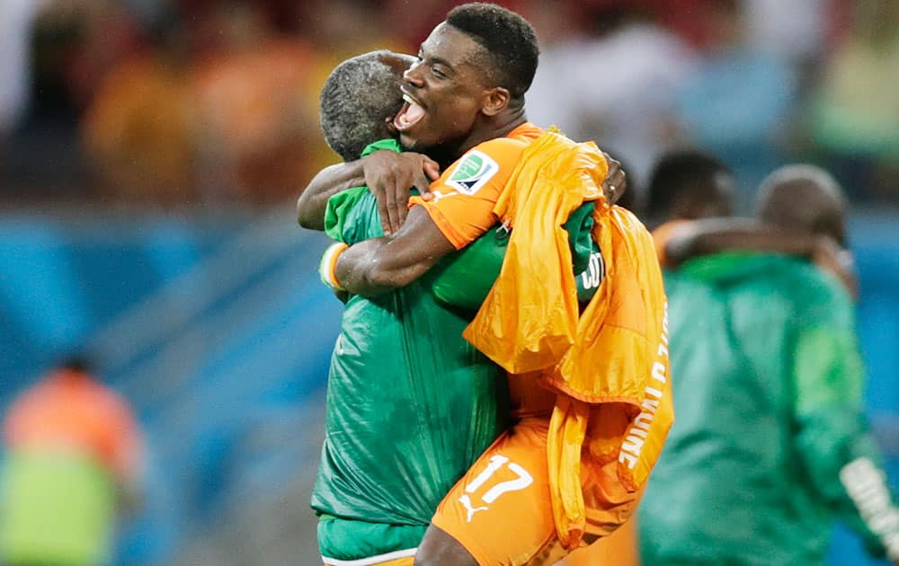 Ivory Coast's Serge Aurier is hugged by a team member after their 2-1 victory over Japan in a group C World Cup soccer match at the Arena Pernambuco in Recife, Brazil.