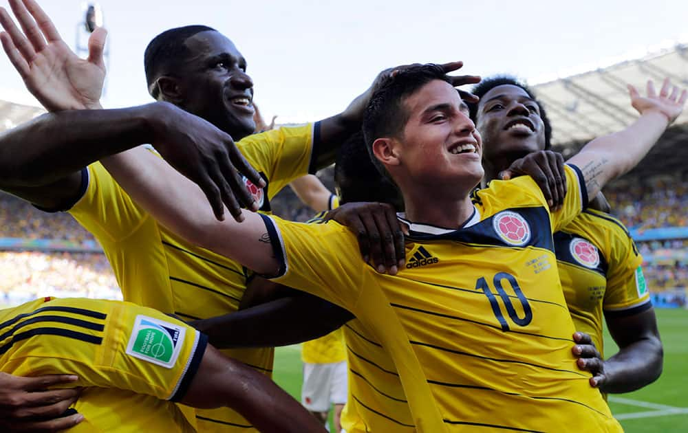 Colombia's James Rodriguez (10) celebrates with his teammates after scoring his side's third goal during the group C World Cup soccer match between Colombia and Greece at the Mineirao Stadium in Belo Horizonte, Brazil.